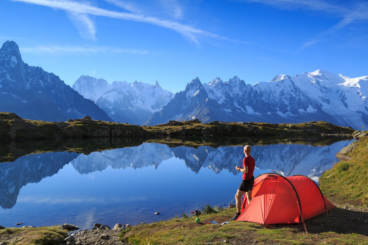 Ein Wanderer steht neben seinem Zelt an einem Bergsee und schaut auf die verschneiten Gipfel.