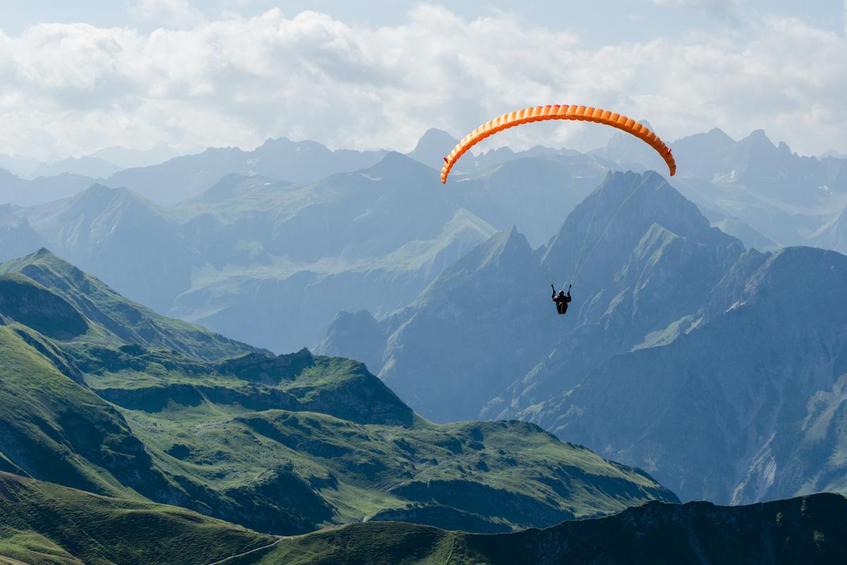 Ein Gleitschirmflieger ist in den Bergen.