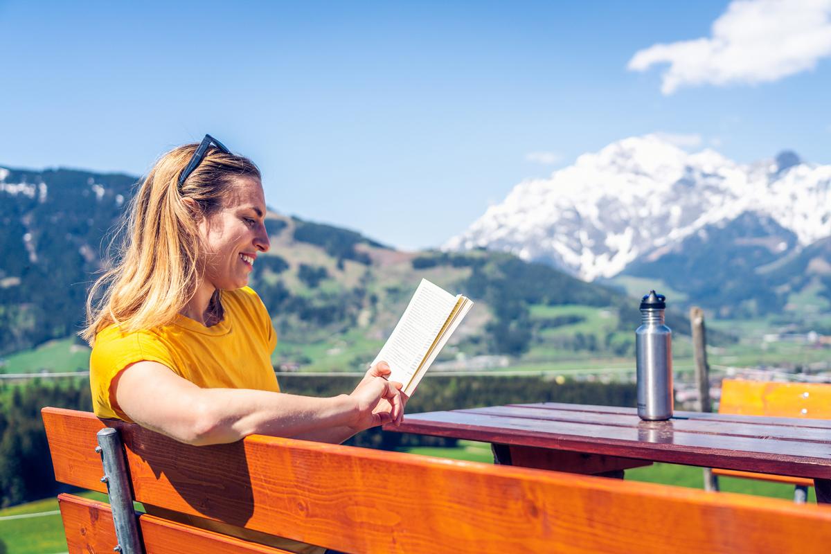 Frau liest Buch in den Bergen