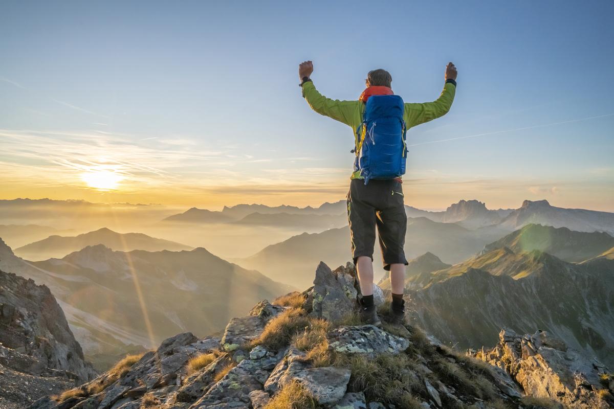 Mann am Gipfel hat ein Berg-Erlebnis