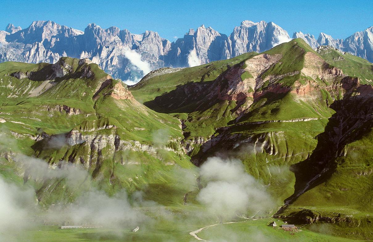 Hinter dem satten Grün der sanften Hochebene Erera-Brendol zeichnen sich die markigen Gipfel der Palagruppe ab – ein toller Kontrast.