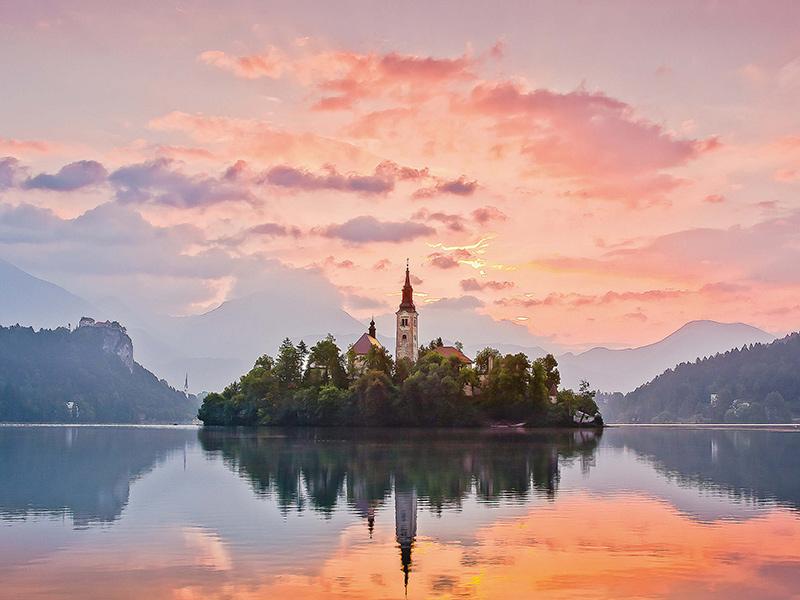 Das erste Tageslicht entflammt den Himmel über dem Bleder See in Slowenien.