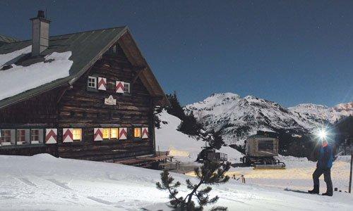 Im Hintergrund der Südwiener Hütte erhellen die Lichter des Wintersportzentrums Obertauern die Nacht.