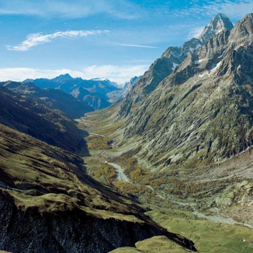 Vom Petit Col de Ferret reicht der Blick weit hinein in den italienischen Arm des Val Ferret Richtung Courmayeur. Rechterhand  ziehen Gletscherzungen hinauf zur Aiguille de Triolet und Aiguille de Leschaux
