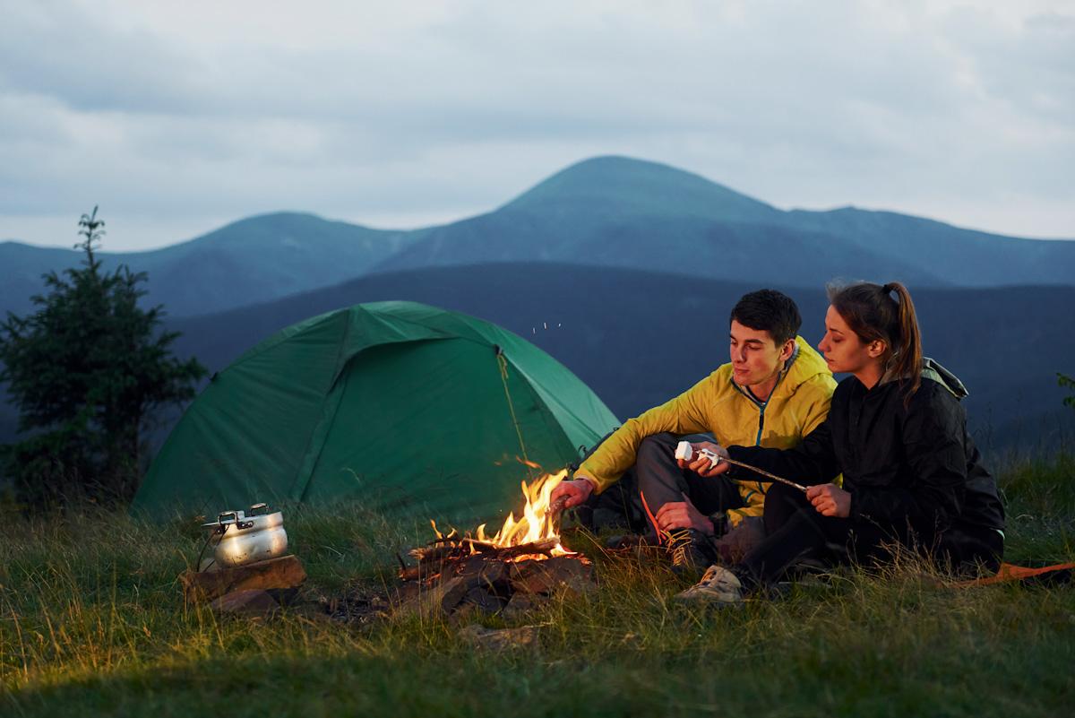 Ein junges Pärchen sitzt vor seinem Zelt in den Bergen am Lagerfeuer und hält Marshmellows in die Flammen.